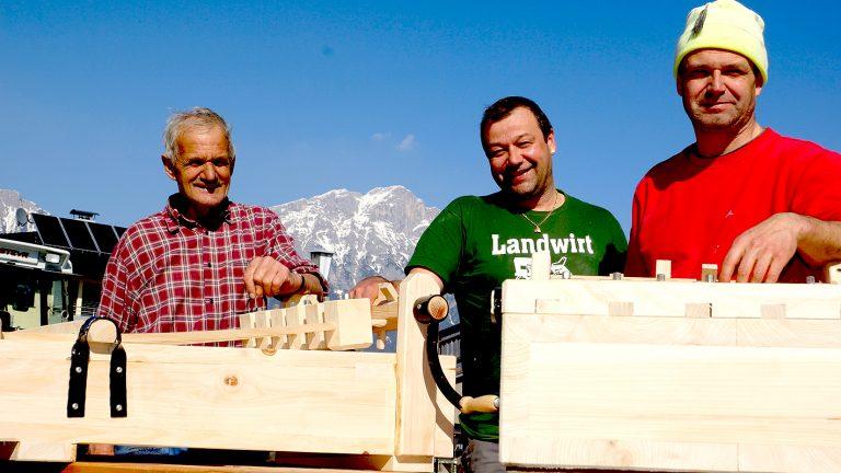 """Anton, Thomas und Christian Schneider bauen die neuen """"Ratschen"""" für den Kirchturm in Untermieming, Foto: Andreas Fischer"""